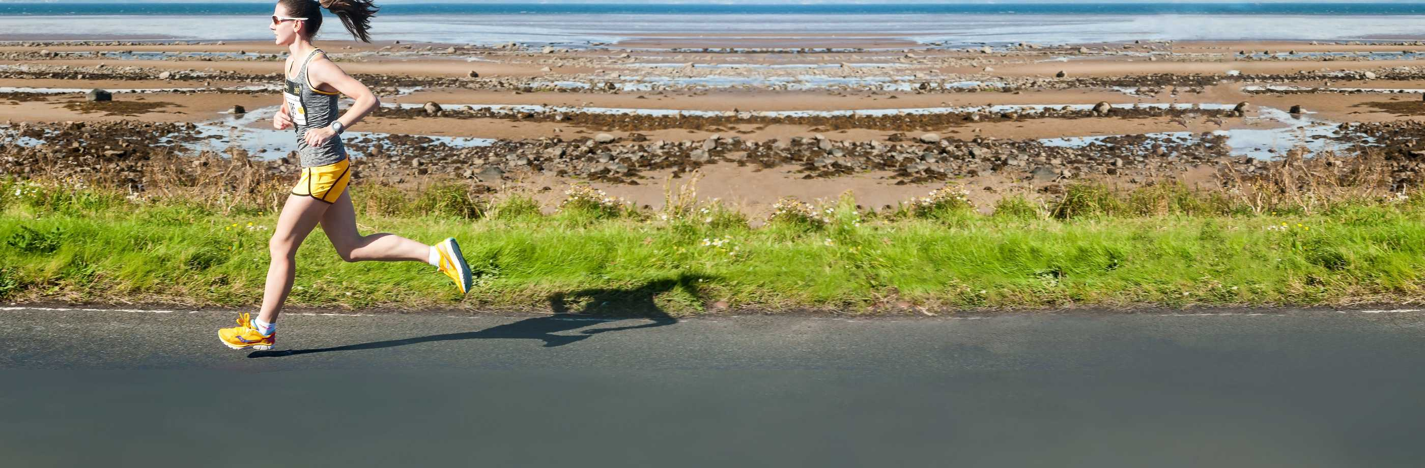 Female runner, racing with estuary in background.