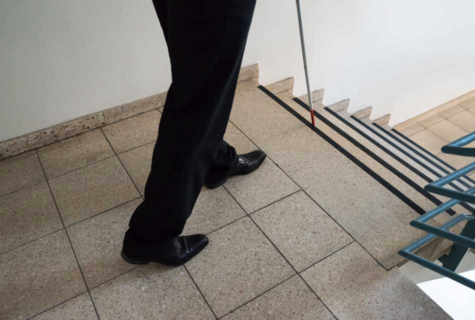 Person walking down the stairs with cane