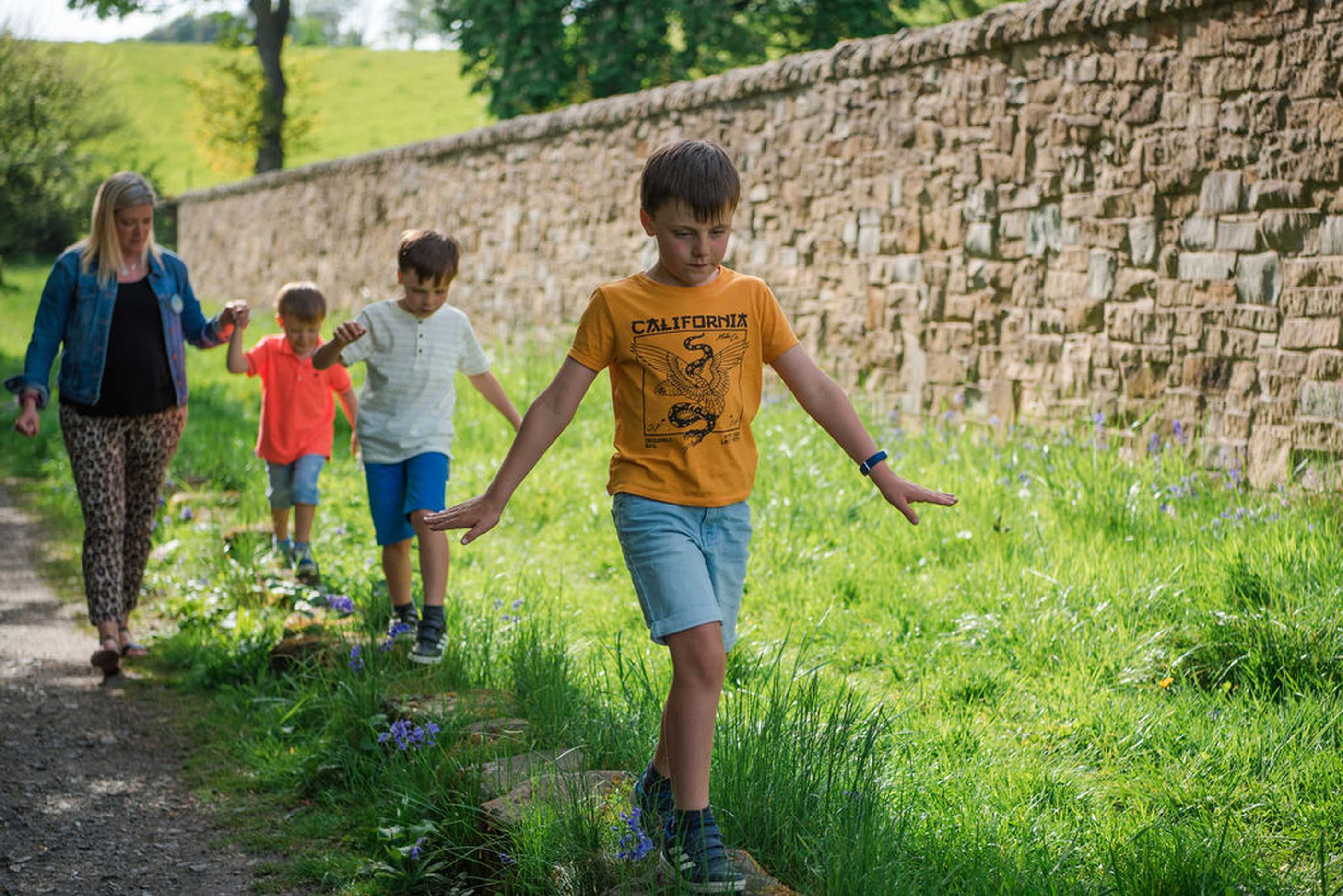 Young boys walking along stones beside a track in summer, the last holding hands with their mother