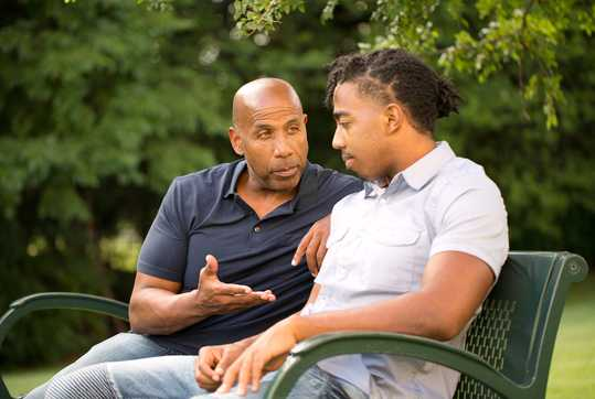 Man mentoring youth on park bench
