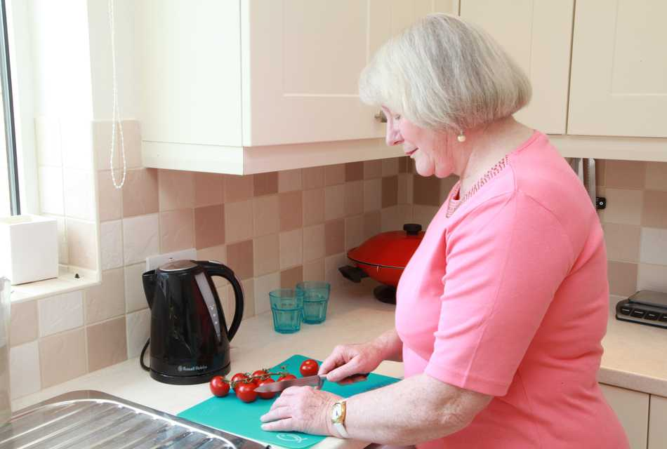 Older lady cutting food on chopping board