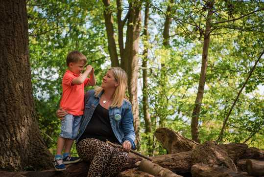Kelly and her son sitting in the woods