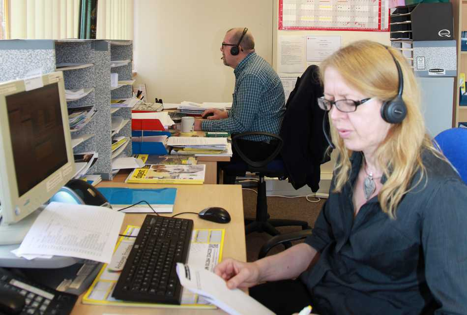 Helpline staff with phone headsets and computers