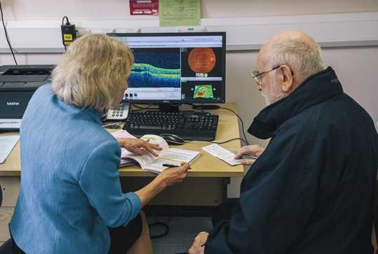 Female consultant, discussing results with male patient with computer images of results.