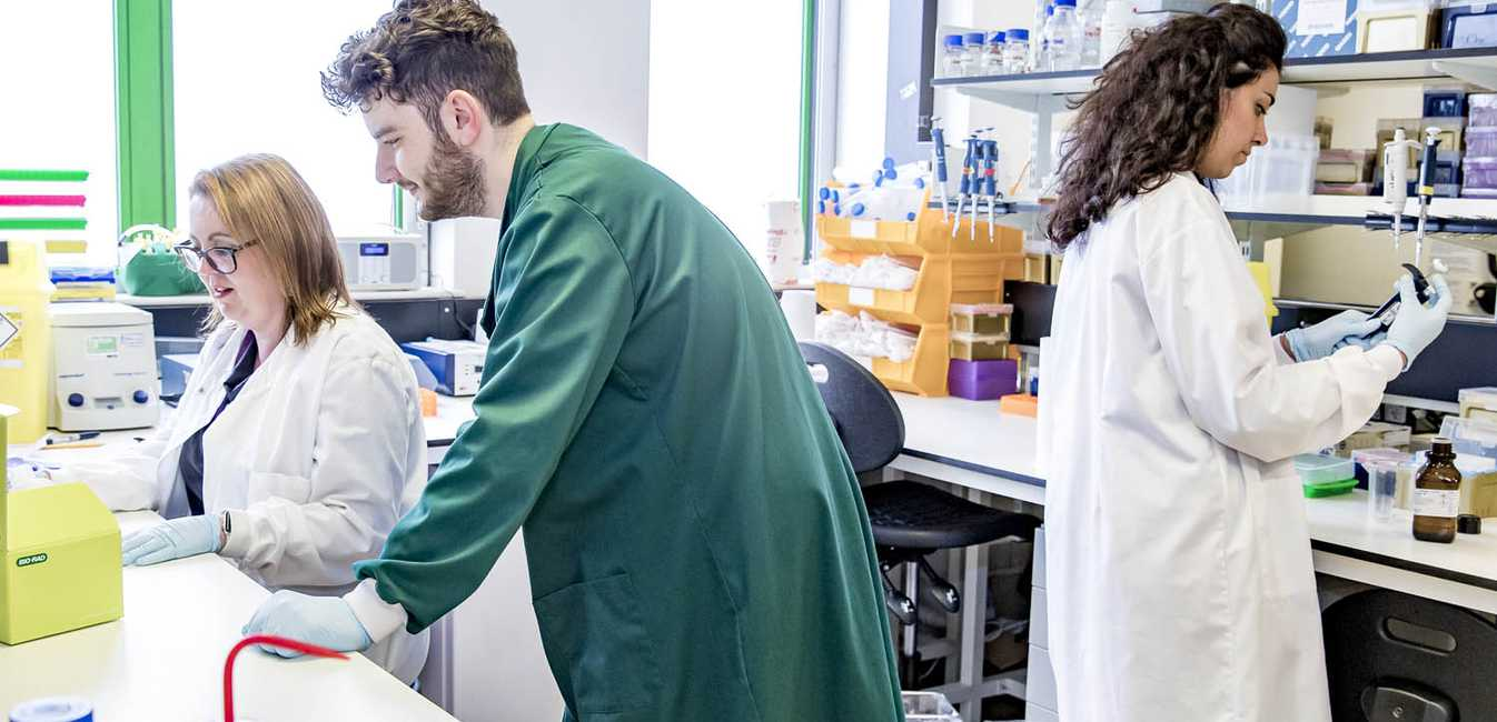 Three researchers in a lab. Man in a green coat in the foreground