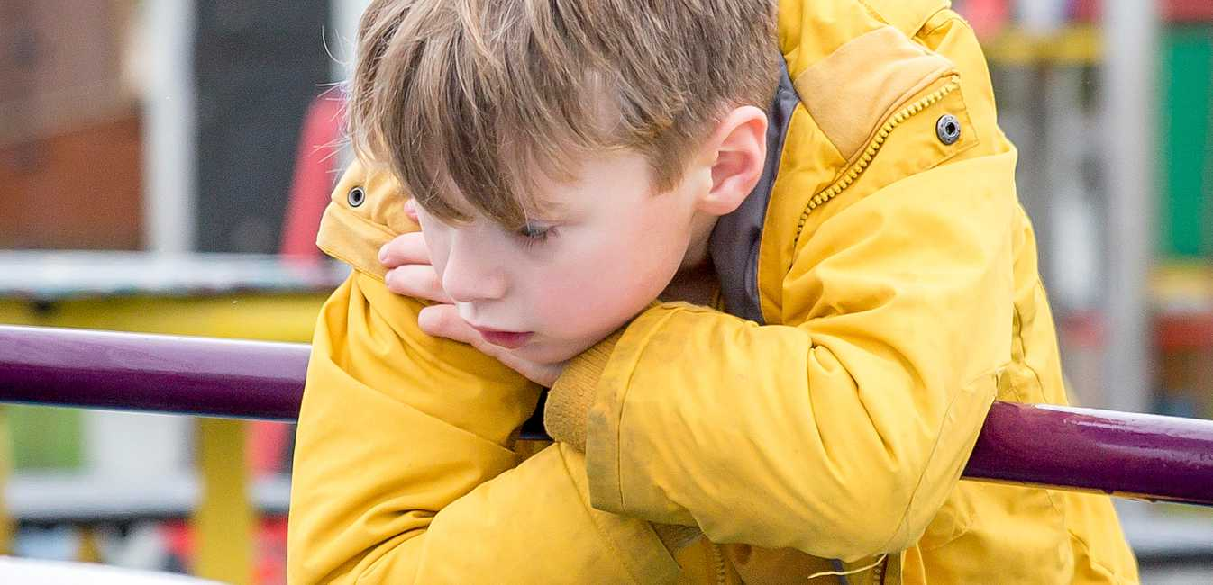Sad young boy wearing a yellow jacket