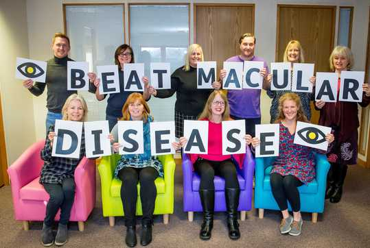 Macular Society staff holding up Beat Macular Disease cards