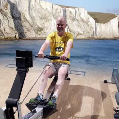 Darren Butler on rowing machine with virtual cliffs of Dover in background