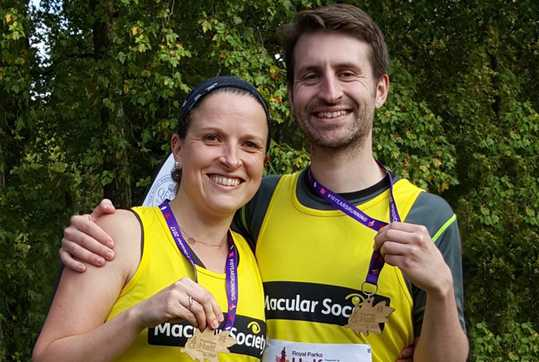 Two runners with vests and medals