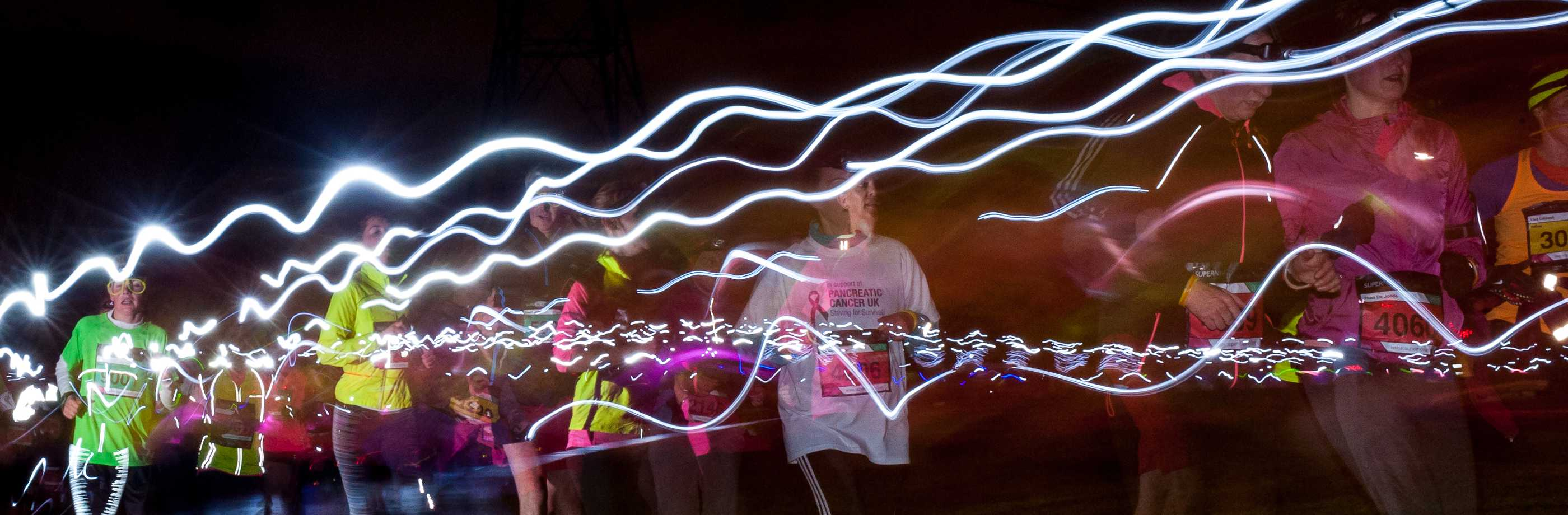 Ghostly runners in the night with light trails above them
