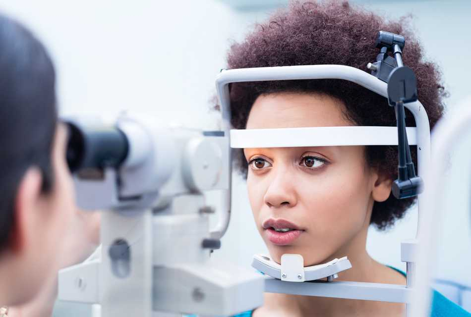 Woman having eye test, resting forehead and chin against machine.
