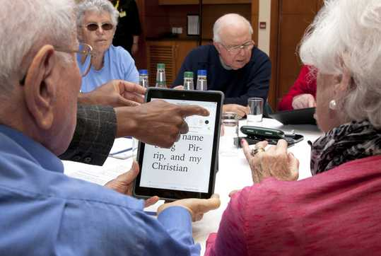 People sitting around table, looking at tablet.