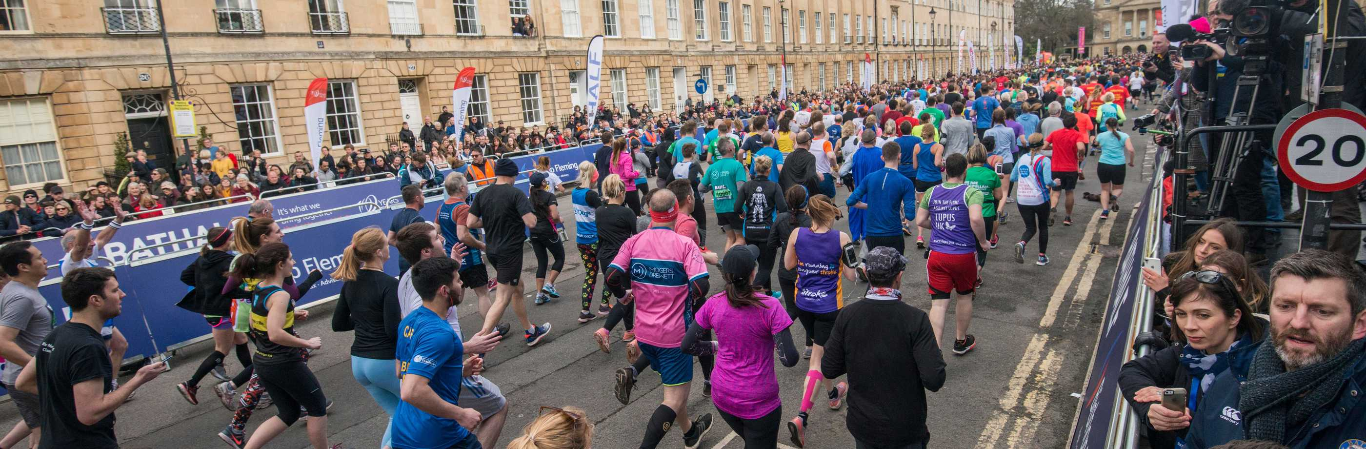 Bath Half runners seen from behind in wide Georgian street