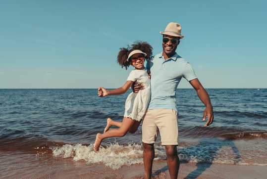 Father and daughter wearing sunglasses on beach
