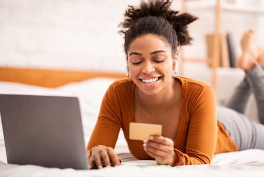 Woman on bed with laptop and credit card