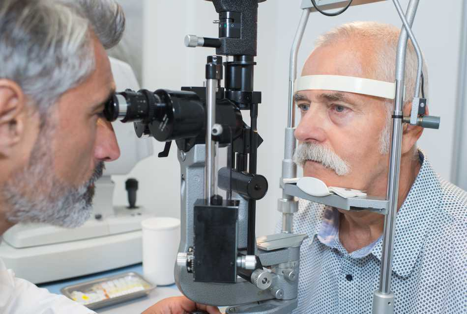 Man having eye test, leaning into eye examination machine.