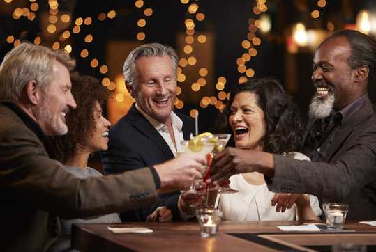Group with drinks celebrating in bar