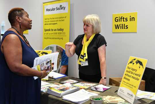 Conference delegate speaking with Macular Society staff at Gifts in Wills table