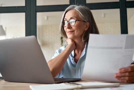 Lady on laptop with papers in hand