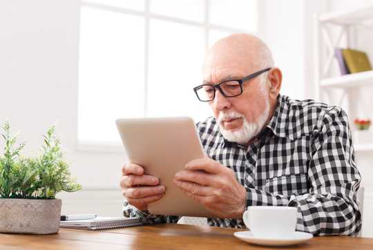 Man with glasses, looking at tablet
