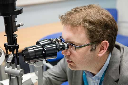 Pearse Keane looking into a microscope